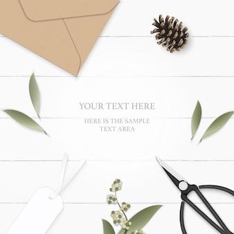 Plat lag bovenaanzicht elegante witte samenstelling papier blad bloem dennenappel kraft envelop tag en vintage metalen schaar op houten achtergrond.