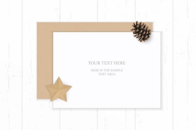 Plat lag bovenaanzicht elegante witte samenstelling papier kraft envelop dennenappel en stervorm ambachtelijke op houten achtergrond.