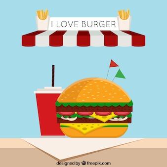 Platte achtergrond met smakelijke hamburger en drank