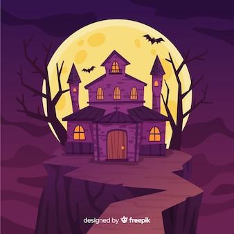 Platte ontwerp van een halloween-huis op een heuvel