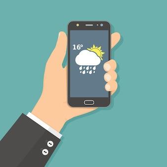 Platte ontwerpconcept met hand met mobiele telefoon met weer-app