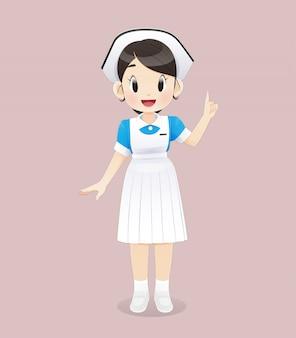 Pleegstudent die een blauw-wit uniform draagt staat op een roze achtergrond. glimlachend vrouwelijk verplegend personeel. illustratie in cartoon characterdesign