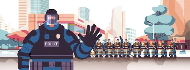 Politieagent in volle tactische versnelling oproerpolitieagent zwaaiende hand demonstranten en demonstraties controle concept stadsgezicht