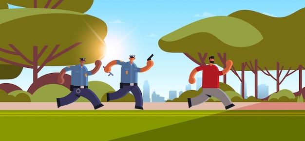 Politieagenten met pistolen achtervolgen inbreker crimineel weglopen van politieagenten in uniforme veiligheidsdienst justitie wet service concept stadspark stadsgezicht achtergrond horizontale volledige lengte