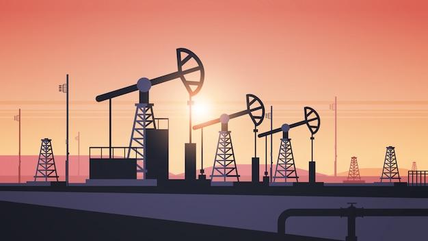 Pomp jack aardolie productie handel olie-industrie concept pompen industriële apparatuur booreiland zonsondergang achtergrond horizontaal