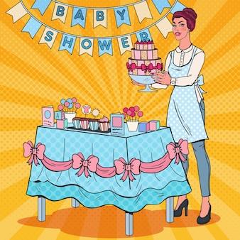Pop art baby shower decorateur met feestdecoratie en cake. viering van de geboorte van een kind.