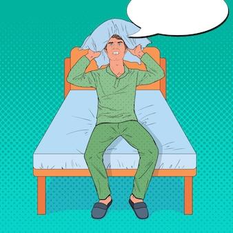 Popart angry man oren met kussen sluiten. stressvolle ochtendsituatie. man die lijdt aan slapeloosheid.