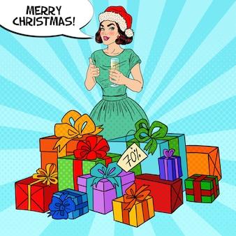 Popart gelukkige vrouw in kerstmuts met grote geschenkdozen en champagneglas.