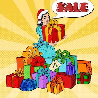 Popart gelukkige vrouw in kerstmuts met grote geschenkdozen op kerstuitverkoop.