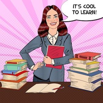 Popart jonge vrouw zittend op de tafel van de bibliotheek en het lezen van boek met hand teken duim omhoog.