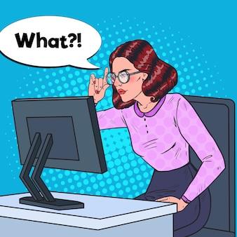 Popart jonge zwak-eyed zakenvrouw in brillen werken op de computer