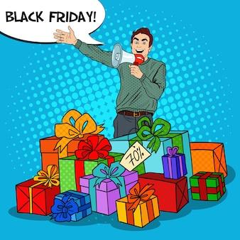 Popart man met megafoon bevordering van grote verkoop staande in geschenkdozen.