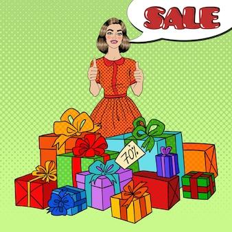 Popart mooie vrouw met enorme geschenkdozen, duimen omhoog en komische tekstballon verkoop.