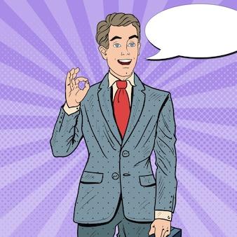 Popart succesvolle zakenman gebaren ok met komische tekstballon. zakelijk succes.
