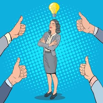 Popart succesvolle zakenvrouw met idee gloeilamp en handen duimen opdagen.
