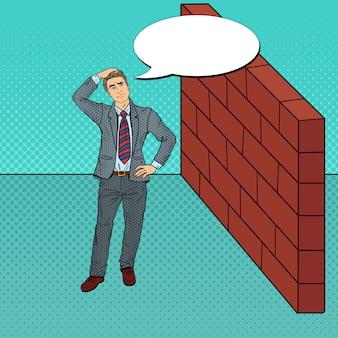 Popart twijfelachtige zakenman permanent voor een bakstenen muur.