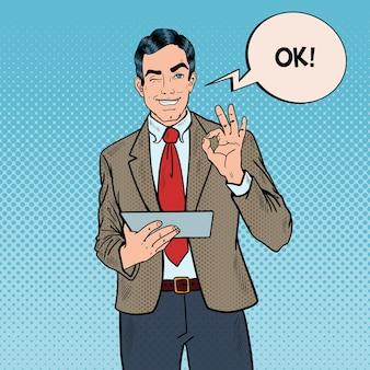 Popart zakenman met tablet gebaren ok en knipogen. illustratie