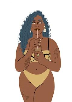 Portret van een vrouw die van een stro in een zwempak op het strand drinkt.