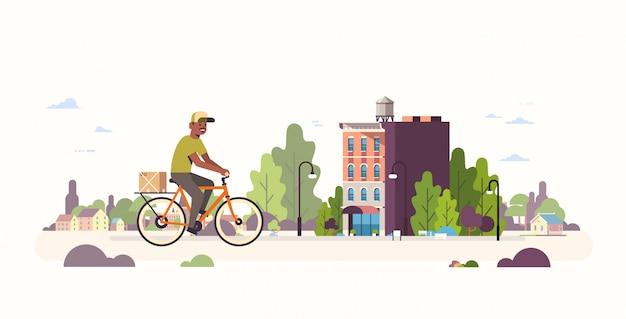 Postbode in uniforme rijdende fiets met kartonnen pakket koerier fietsen buitenshuis express levering service concept moderne stadsgezicht achtergrond volledige lengte horizontaal