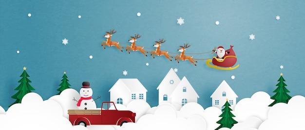 Prettige kerstdagen en een gelukkig nieuwjaar met rendieren en de kerstman in slee vliegen in de lucht over dorp in papier gesneden stijl.