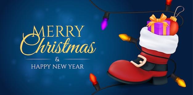 Prettige kerstdagen en een gelukkig nieuwjaarsbanner. rode kerstman laars gevuld met een geschenkdoos en een balspeelgoed met een kleurrijke slinger erop.
