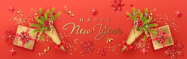 Prettige kerstdagen en gelukkig nieuwjaar banner met een boeket van dennentakken in een wafelkegel en geschenken
