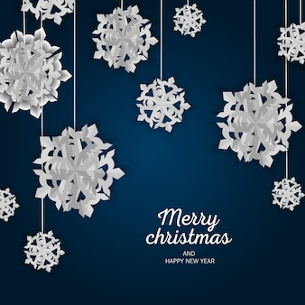 Prettige kerstdagen en gelukkig nieuwjaar groet blauw met realistische gesneden papieren sneeuwvlokken.