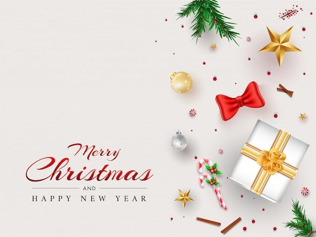 Prettige kerstdagen en gelukkig nieuwjaar wenskaart met bovenaanzicht van geschenkdoos, kerstballen, sterren, snoepgoed en pijnboombladeren ingericht op wit.