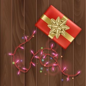 Prettige kerstdagen of gelukkig nieuwjaarsdag wenskaart met een rode geschenkdoos met gouden strik