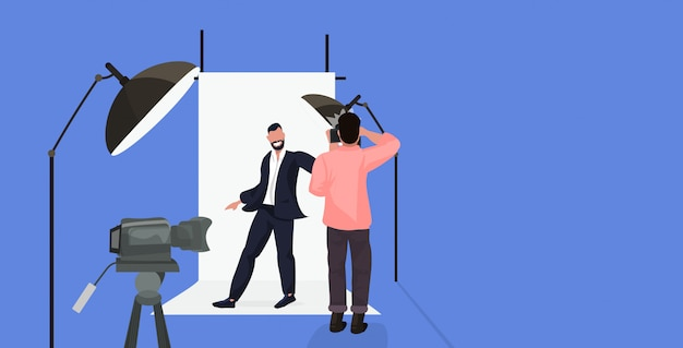 Professionele fotograaf die cameramens schieten zakenman in het formele slijtage stellen in moderne fotostudio horizontale volledige lengte