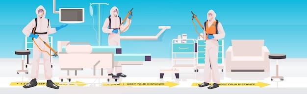 Professionele schoonmakers in hazmat pakken conciërges die het coronavirus reinigen en desinfecteren