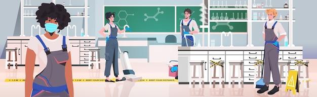 Professionele schoonmakers mix race conciërges team schoonmaken en desinfecteren school