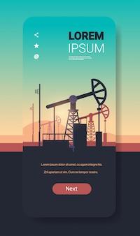 Pumpjack aardolieproductie handel olie-industrie concept pompen industriële apparatuur booreiland zonsondergang achtergrond smartphone scherm mobiele app verticale kopie ruimte