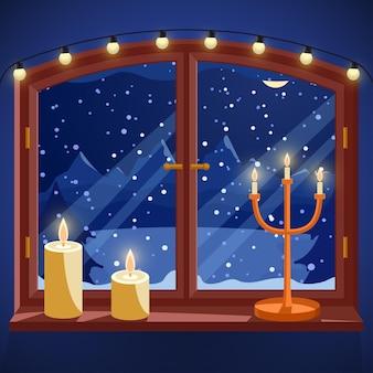 Raam met winterzicht 's nachts kaarsen kandelaar en lichte slinger op vensterbank besneeuwd bos