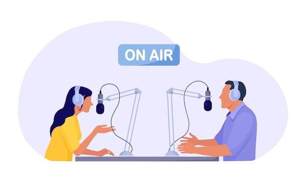 Radiopresentator interviewt gasten op radiostation. man en vrouw in koptelefoon praten met microfoons die podcast opnemen in de studio. massamedia uitzendingen