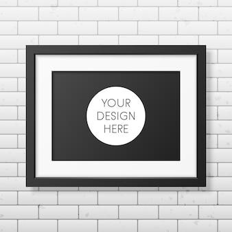 Realistisch zwart frame a4 op de bakstenen muur