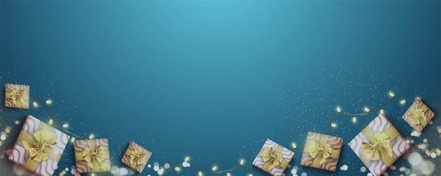 Realistische achtergrond met geschenkdozen en gouden glitter decoratief licht