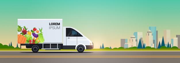Realistische bestelwagen met biologische groenten op stad snelweg natuurlijke veganistische boerderij eten bezorgservice voertuig met verse groenten stadsgezicht achtergrond horizontale flat