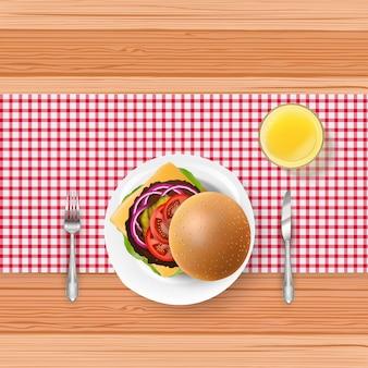 Realistische hamburger met vork en mes op houten lijst