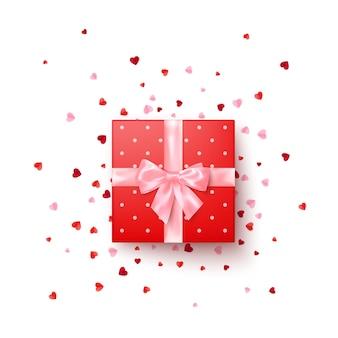 Realistische rode geschenkdoos met roze zijden strik versierd confetti bovenaanzicht