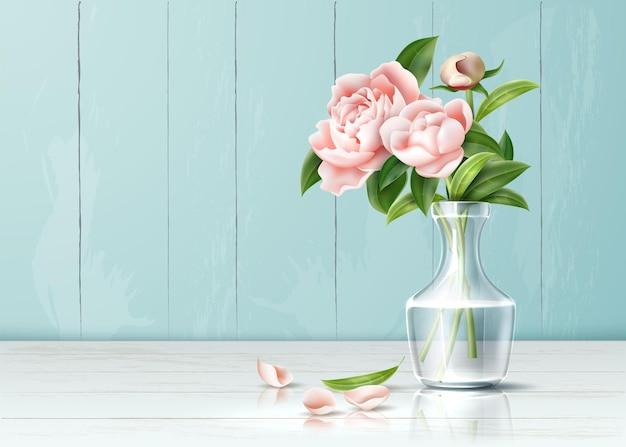 Realistische roze bloemen met bladerenboeket in transparante vaas met vallende bloemblaadjes aan tafel