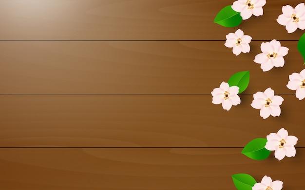Realistische witte bloemen en groene bladeren op houten textuurachtergrond
