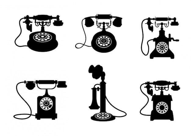 Reeks retro en uitstekende telefoons die op witte achtergrond wordt geïsoleerd
