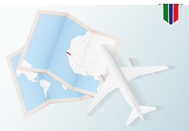 Reis naar gambia, bovenaanzicht vliegtuig met kaart en vlag van gambia.