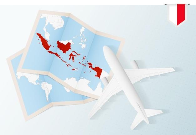 Reis naar indonesië, bovenaanzicht vliegtuig met kaart en vlag van indonesië.