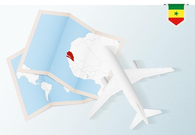 Reis naar senegal, bovenaanzicht vliegtuig met kaart en vlag van senegal.