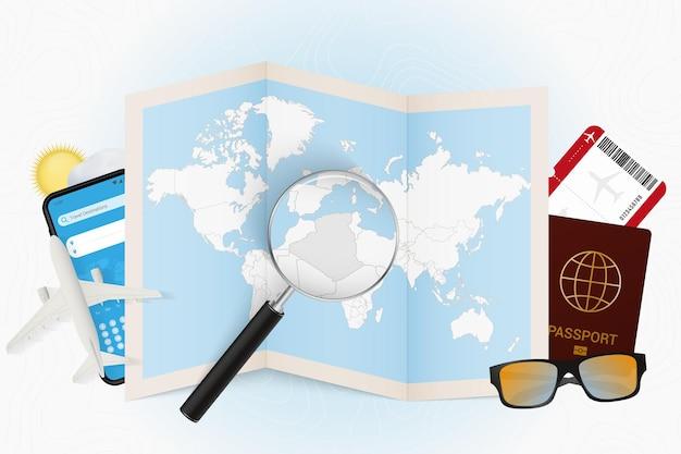 Reisbestemming algerije, toerismemodel met reisuitrusting en wereldkaart met vergrootglas op algerije.