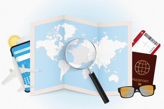 Reisbestemming frankrijk, toerismemodel met reisuitrusting en wereldkaart met vergrootglas op frankrijk.