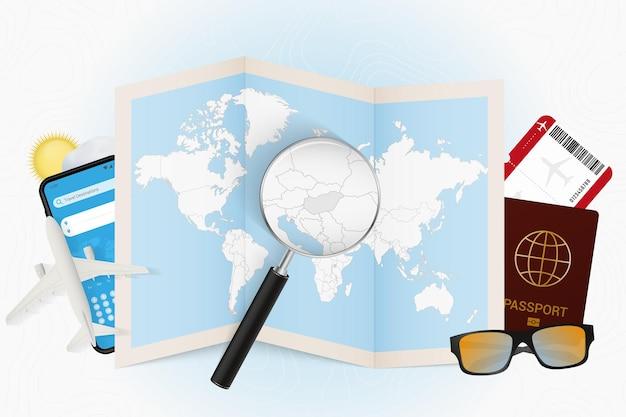 Reisbestemming hongarije, toerismemodel met reisuitrusting en wereldkaart met vergrootglas op hongarije