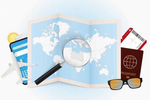 Reisbestemming libië, toerismemodel met reisuitrusting en wereldkaart met vergrootglas op libië.